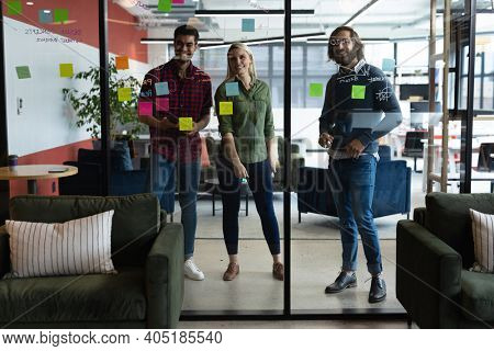 Diverse group of business people working in creative office. group of people brainstorming and taking notes on glass board. business people and work colleagues at a busy creative office.