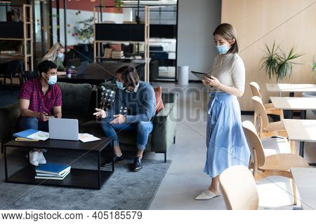 Diverse group of business people working in creative office. group of people wearing face masks and discussing work. social distancing protection hygiene in workplace during covid 19 pandemic.