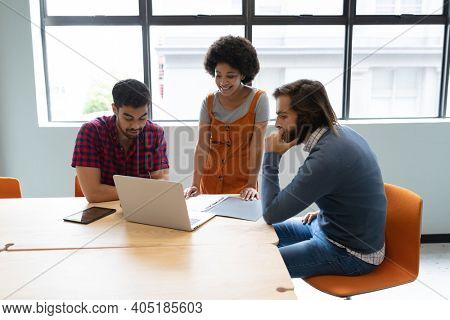 Diverse group of business people working in creative office. group of people discussing work and using laptop. business people and work colleagues at a busy creative office.