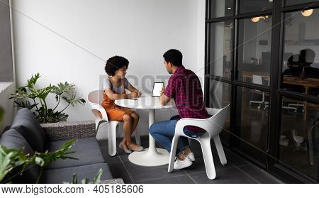 Two mixed race business people working in creative office. two people sitting and discussing work. business people and work colleagues at a busy creative office.