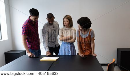 Diverse group of business people working in creative office. group of people standing and discussing work. business people and work colleagues at a busy creative office.