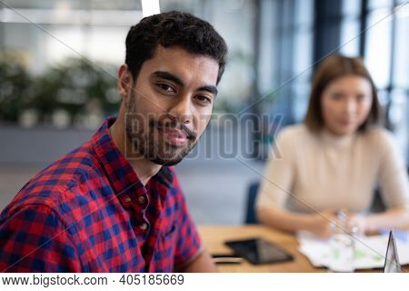Diverse group of business people working in creative office. portrait of a man looking at camera and smiling. business people and work colleagues at a busy creative office.