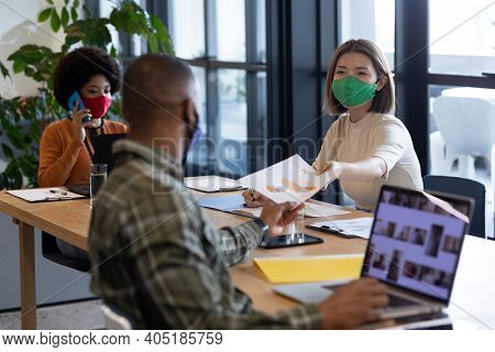 Diverse group of business people working in creative office. group of people wearing face masks and giving documents. social distancing protection hygiene in workplace during covid 19 pandemic.