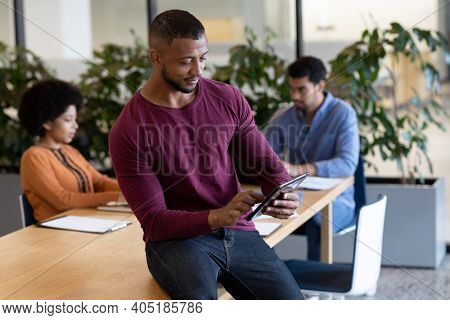 Diverse group of business people working in creative office. man sitting on a table and using tablet. business people and work colleagues at a busy creative office.