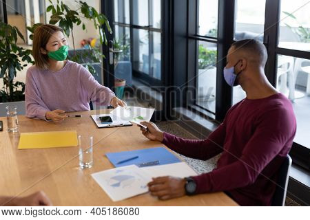Two diverse business people working in creative office. two people in a meeting discussing work. social distancing protection hygiene in workplace during covid 19 pandemic.