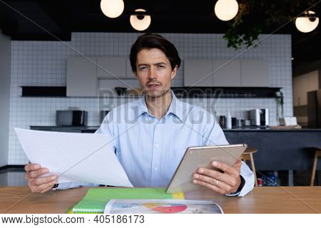 Caucasian businessman sitting having video chat going through paperwork using digital tablet in modern office. business modern office workplace technology.