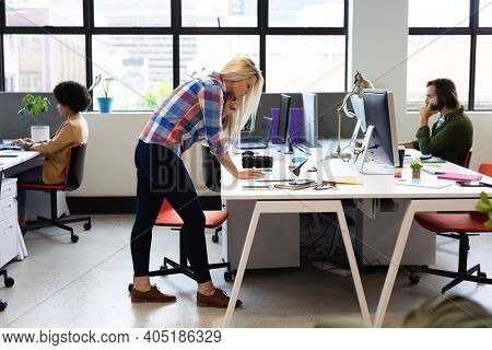 Caucasian businesswoman standing at desk using laptop computer in office. with colleagues in the background. business people and work colleagues at a busy creative office.
