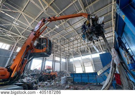 Waste Sorting And Recycling Plant. Loader And Grab Crane Are Handling Waste.