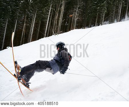Side View Snapshot Of Skier Sliding Down The Piste Along Spruce Forest. Moment Of Fall Down On Snow.