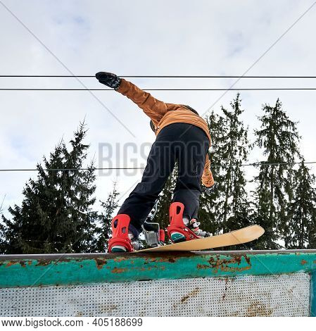 Rear View Of Leaned Snowboarder Trying To Keep Balance, Low Angle View. Sportsman Wearing Colorful V