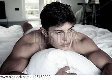 Portrait Of Handsome Topless Muscular Hispanic Man In Bed, Looking Away From Camera.