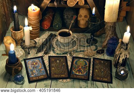 Fortune Telling Ritual With Tarot Cards, Burning Candles, Cup Of Tea And Crystals On Wooden Table. E