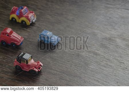 Children's Imaginary Concept Games. Little Toy Cars Racing Headlong Across A Brown Wooden Surface. V