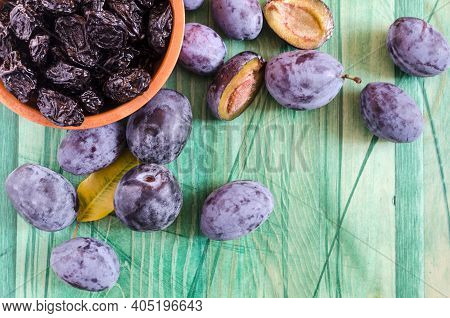 Plum And Dried Plum On A Wooden Background Top View Prunes