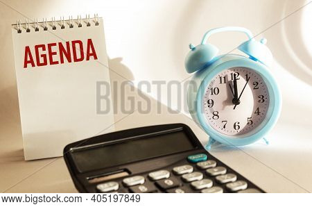 Business Agenda, Planning Concept. Spiral Notebook With Agenda Text On White Background. Flat Lay Or