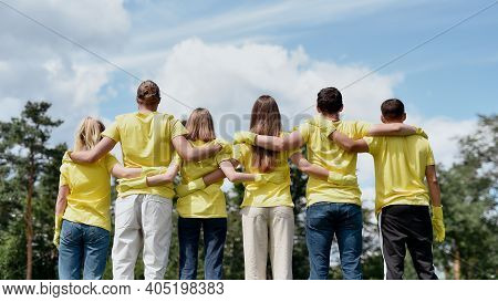 Clean Up Day. Group Of Young Volunteers Wearing Uniform And Rubber Gloves Hugging And Looking At Gre