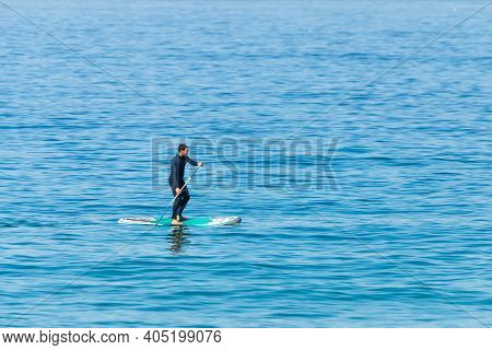 Portugal, Praia Santa Rita Norte, October 04, 2018: Stand Up Paddle Boarder In Wetsuit Paddling On A