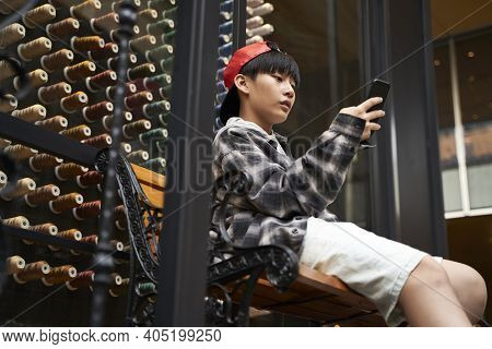 Fifteen-year-old Teenage Asian Boy Sitting On Bench Looking At Cellphone