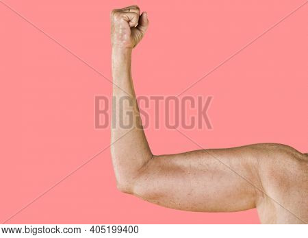 Woman flexing her muscles against pink backdrop to show power of woman or feminism