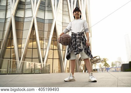 Low Angle Outdoor Portrait Of A Fifteen-year-old Asian Teenage Basketball Player