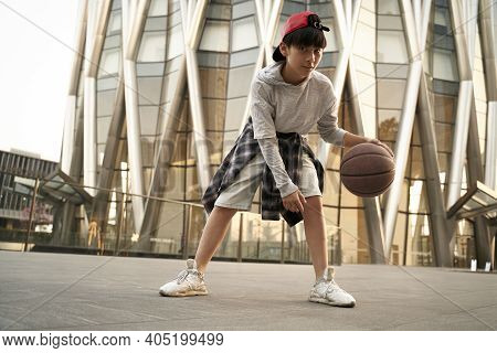Fifteen-year-old Teenage Asian Boy Playing Basketball Outdoors In Front Of A Modern Building