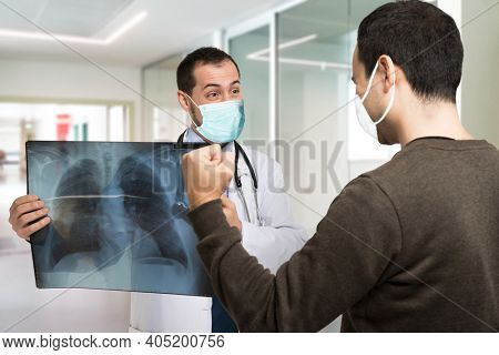 Doctor showing a radiography to an happy patient, covid coronavirus cure concept