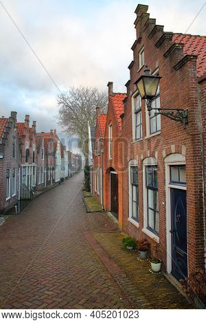Colorful Facades Of Historic Houses Along A Paved Street In Edam, North Holland, Netherlands