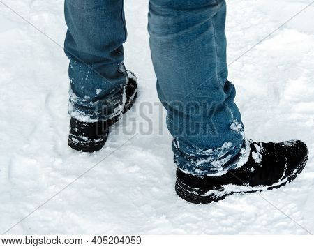 The Legs Of A Man In Blue Jeans And Snow-covered Black Boots On A Snow Trail Close-up. Advertising H