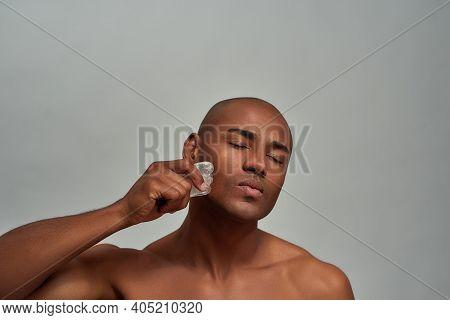 Man Keeping His Eyes Closed While Scraping His Cheek With Crystal Facial Lifting Tool