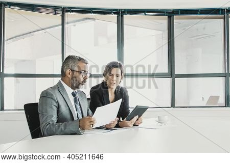 Company Executives Analyzing And Discussing Reports. Two Business Colleagues Sitting Together, Looki