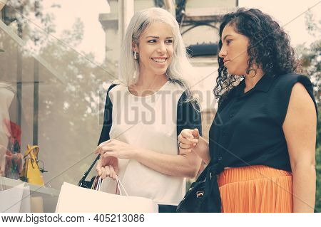 Happy Female Friends Standing At Shop Window With Accessories, Holding Shopping Bags, Smiling And Ch