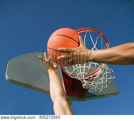 Young man playing basketball with friend against blue sky