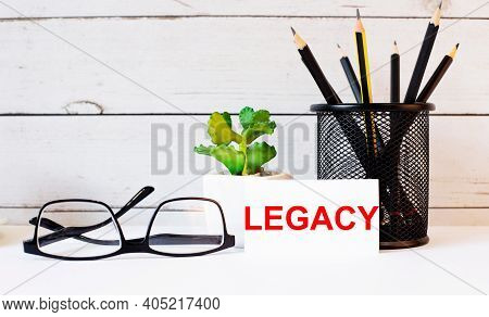 The Word Legacy Written On A White Business Card Next To Pencils In A Stand And Glasses. Nearby Is A