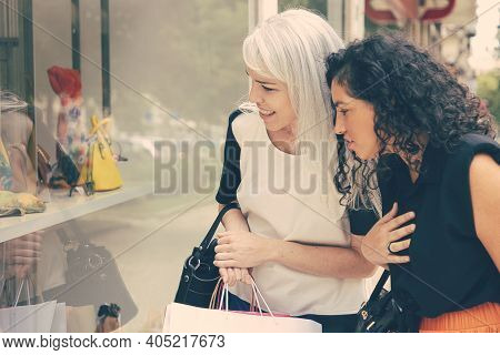 Excited Female Friends Holding Shopping Bags, Standing At Store Outside, Staring At Accessories In S