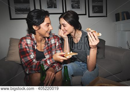 Two Happy Young Girls Laughing, Drinking Beer, Sharing Pizza At Home Party Late. Cheerful Best Frien
