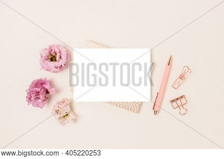 Blank Paper Card Mockup, Stationery And Eustoma Flowers On A Beige Background. Feminine Workspace Wi