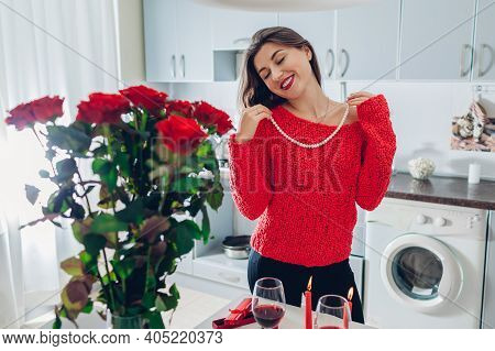 Young Woman Found Bouquet Of Roses With Candles, Wine And Gift On Kitchen. Happy Girl Tries On Pearl