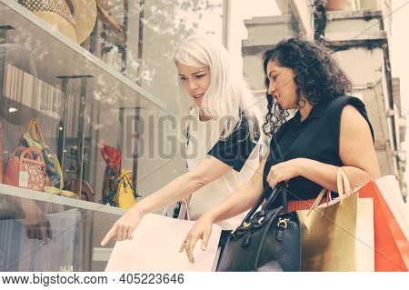 Two Female Shoppers Pointing And Staring At Accessories In Shop Window, Holding Shopping Bags, Stand