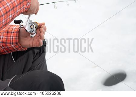 Fisherman Fishing On A Frozen Lake In Winter With Fishing Pole Or Rod, Ice Auger And Equipment For F