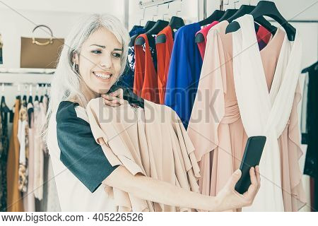 Happy Woman Shopping In Clothes Store And Consulting Friend On Cellphone, Showing Chosen Dress At Fr