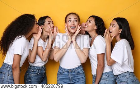 Excited Young Women Gossiping Sharing Rumors And Whispering Secrets Standing Over Yellow Studio Back