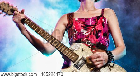 Female rock guitarist on stage in concert