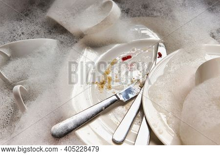Stack of dirty dishes and silverware in sink