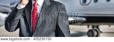 Businessman using cell phone with private jet in background