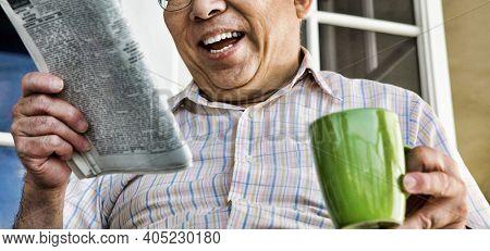 Senior Man Reading Newspaper while drinking coffee