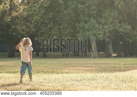 Fair Haired Little Girl Standing On Grass In Park. Full Length, Wide Shot, Copy Space. Childhood And