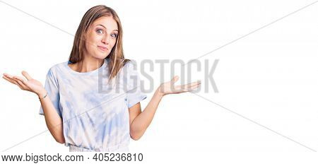 Young beautiful blonde woman wearing tye die tshirt clueless and confused expression with arms and hands raised. doubt concept.