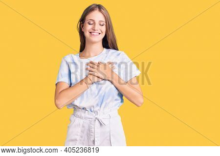 Young beautiful blonde woman wearing tye die tshirt smiling with hands on chest with closed eyes and grateful gesture on face. health concept.