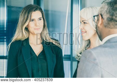 Businesswoman Standing In Office And Talking With Colleagues. Young Confident Employee Meeting With