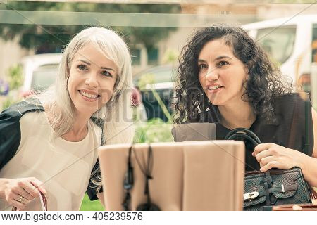 Cheerful Female Shoppers Staring At Accessories In Shop Window, Holding Shopping Bags, Standing At S